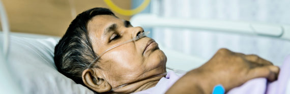 woman with breathing tubes in hospital bed