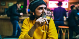 Man in yellow sweater drinking beer
