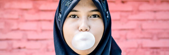 young muslim woman with bubblegum