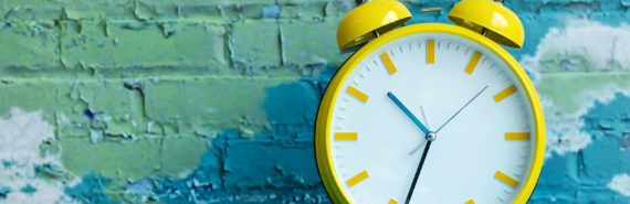 clock against colorful painted brick wall