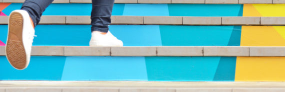 person in white sneakers runs up colorful stairs