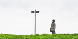 person at crossroads on green grass