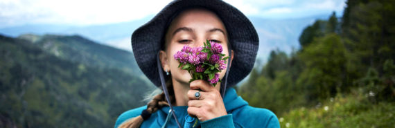 girl on mountain smells flowers