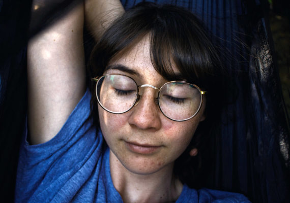woman meditates in hammock