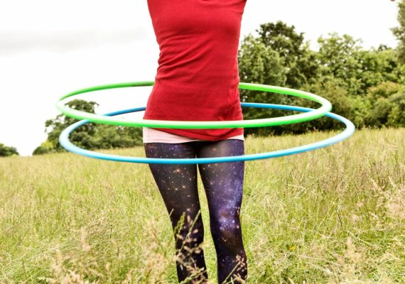 person uses two hula hoops in field