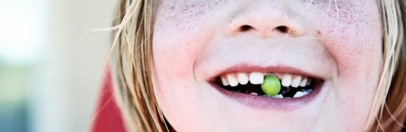 girl with pea in place of missing tooth