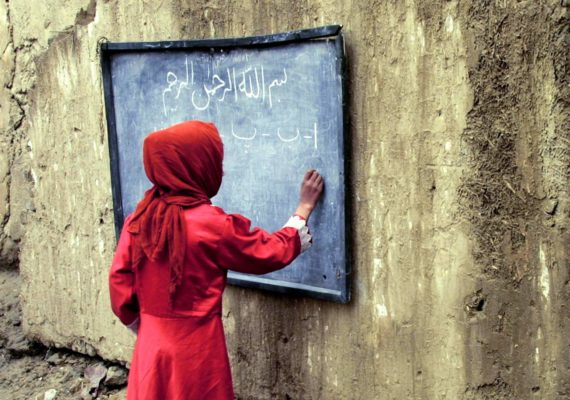 girl in red writes on chalkboard