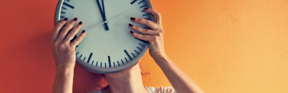 woman holds clock in front of face