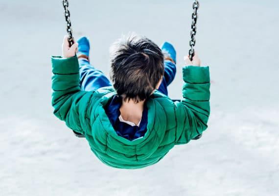 child swinging alone
