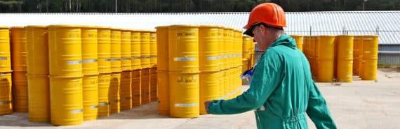 worker walks by nuclear waste barrels