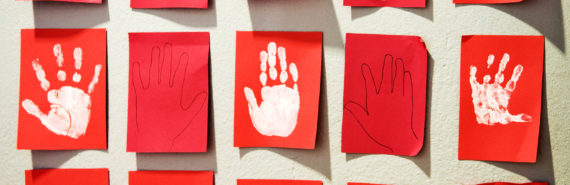 child handprints on red paper