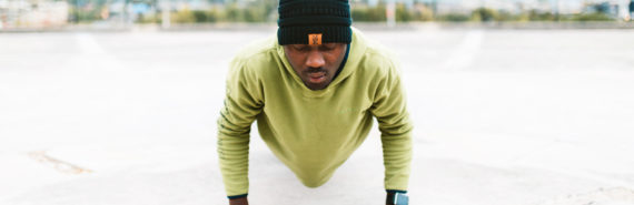 man in green sweatshirt does push-up