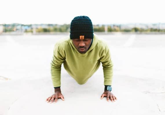 man in green sweatshirt does push-up