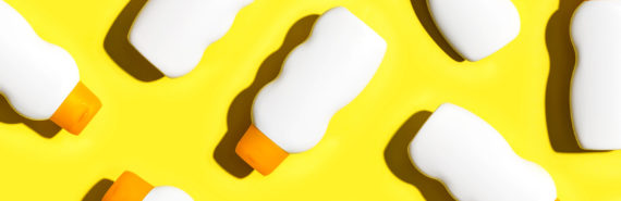 white sunscreen bottles on yellow