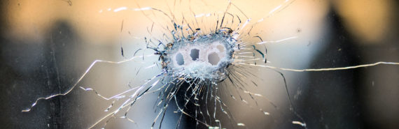 bullet holes in glass (gun laws and domestic partner violence concept)