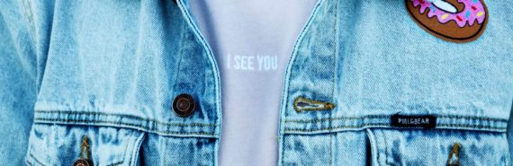 "t-shirt under jean jacket says ""I see you"""