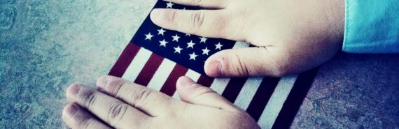 child's hands on the flag of the United States