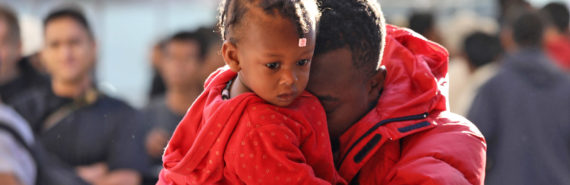 Haitian refugee man holds toddler girl