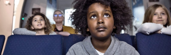 children in theater watching something