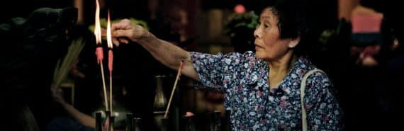 woman lights joss sticks in temple