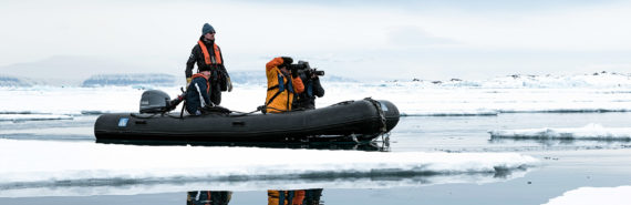 people in kodiak boat in svalbard, arctic