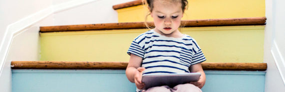 young girl reading iPad on stairs (speech recognition apps and literacy concept)