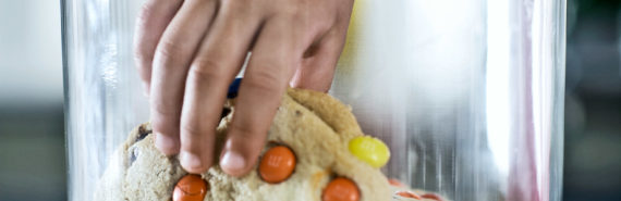 child's hand in cookie jar (stress eating concept)
