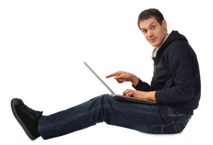 Young man with laptop sits on floor