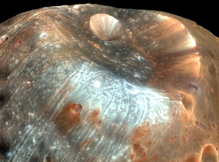 The Stickney Crater on Phobos. The High Resolution Imaging Science Experiment (HiRISE) camera on NASA's Mars Reconnaissance Orbiter took two images of the larger of Mars' two moons, Phobos, within 10 minutes of each other on 23 March 2008. This is the first, taken from a distance of about 6,800 kilometers (about 4,200 miles). It is presented in color by combining data from the camera's blue-green, red, and near-infrared channels. (Credit: NASA/JPL-Caltech/University of Arizona)