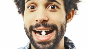 man with a pill in his mouth