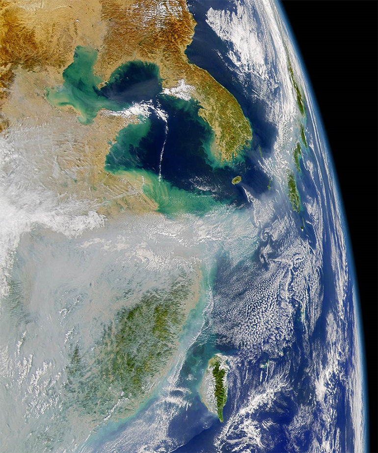Satellite photo shows huge air pollution clouds at far left. Japan is on the right. (Credit: NASA JPL)