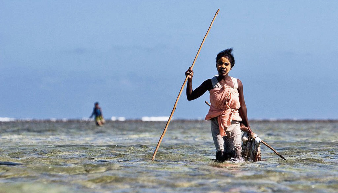 young women with spear in ocean