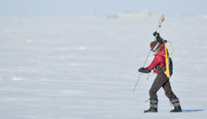 Melinda Webster measures snow depth in the Arctic