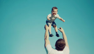 father tosses kid in the air