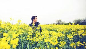 man in field of yellow flowers