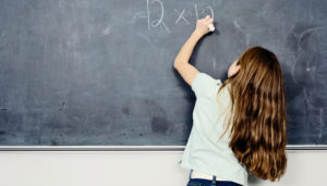 student writes on chalkboard