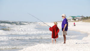 man and boy fish from shore in Gulf of Mexico
