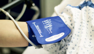 blood pressure cuff on hospital patient's arm