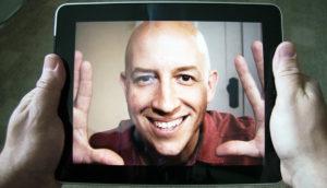 man's face on an iPad