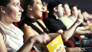 woman eats popcorn at the movie theater