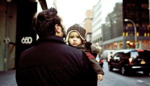 man carries toddler in neighborhood