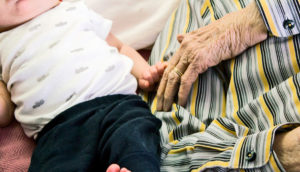 baby and elderly man holding hands