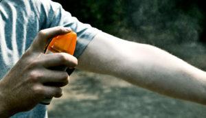 man sprays DEET on arm