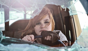 girl in a car with a shattered windshield