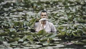 man in the water with a fish in his mouth