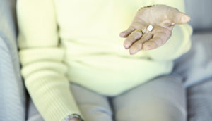 an older woman holding a white pill