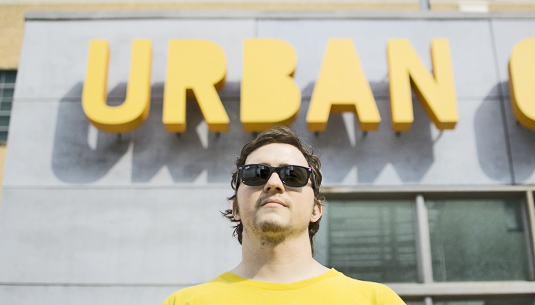 "man stands under a sign that reads ""urban"""