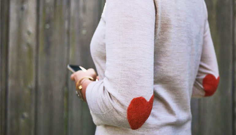 woman wears a sweater with heart-shaped patched on the elbows