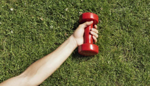 arm, hand hold red weight on grass