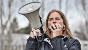 woman speaks into bullhorn at protest
